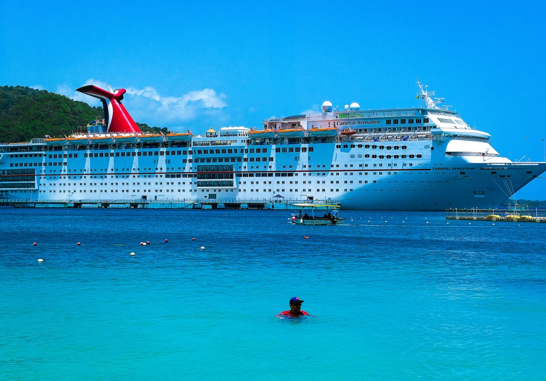 A man in red and blue floats in front of a docked Carnival Cruise Ship and small tourist boat in Moon Palace Cove in Ochos Rios Jamaica.