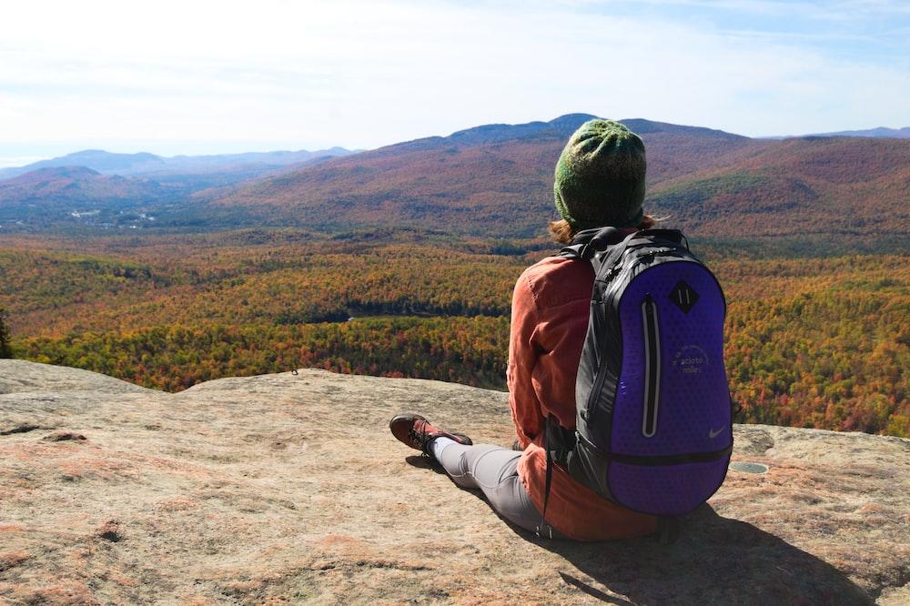 man in orange jacket and black pants sitting on brown rock during daytime