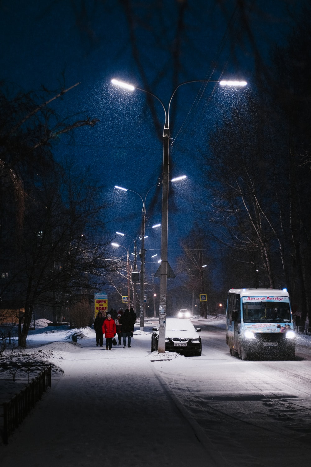 people walking on snow covered road during night time
