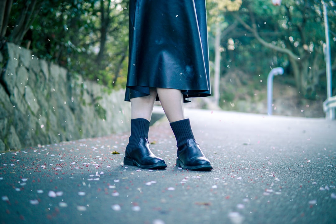 Person In Black Rain Boots Walking On Road During Daytime - unsplash