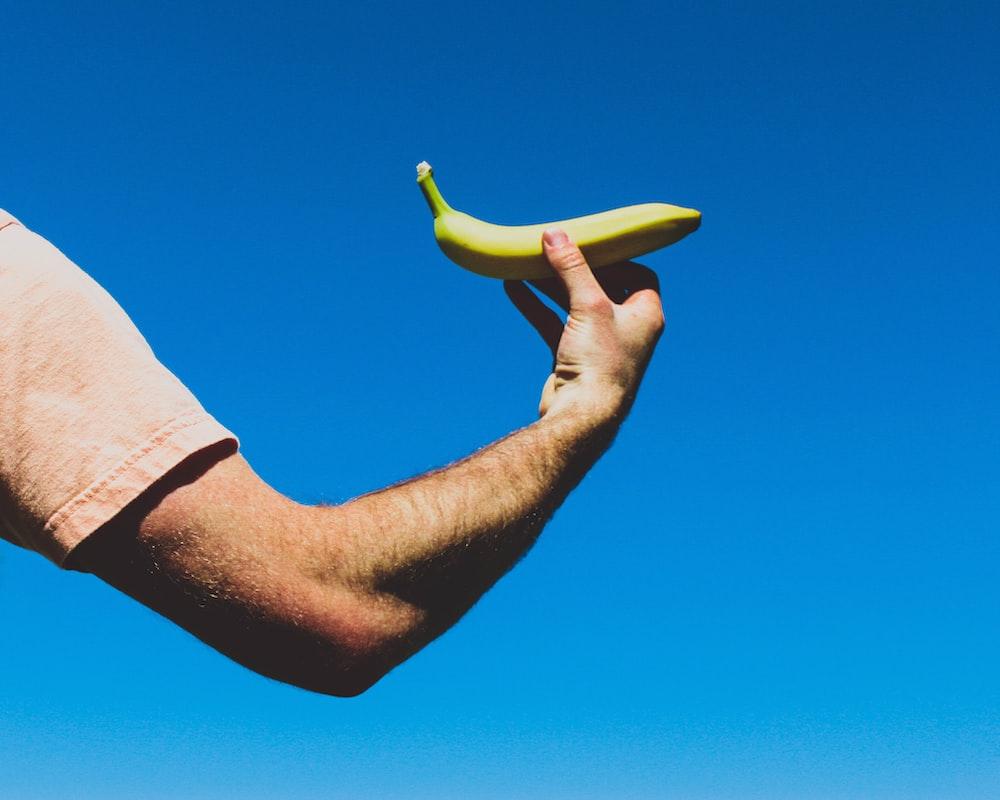 person holding green banana fruit