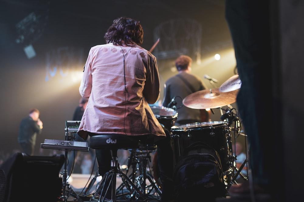 man in white dress shirt playing drum