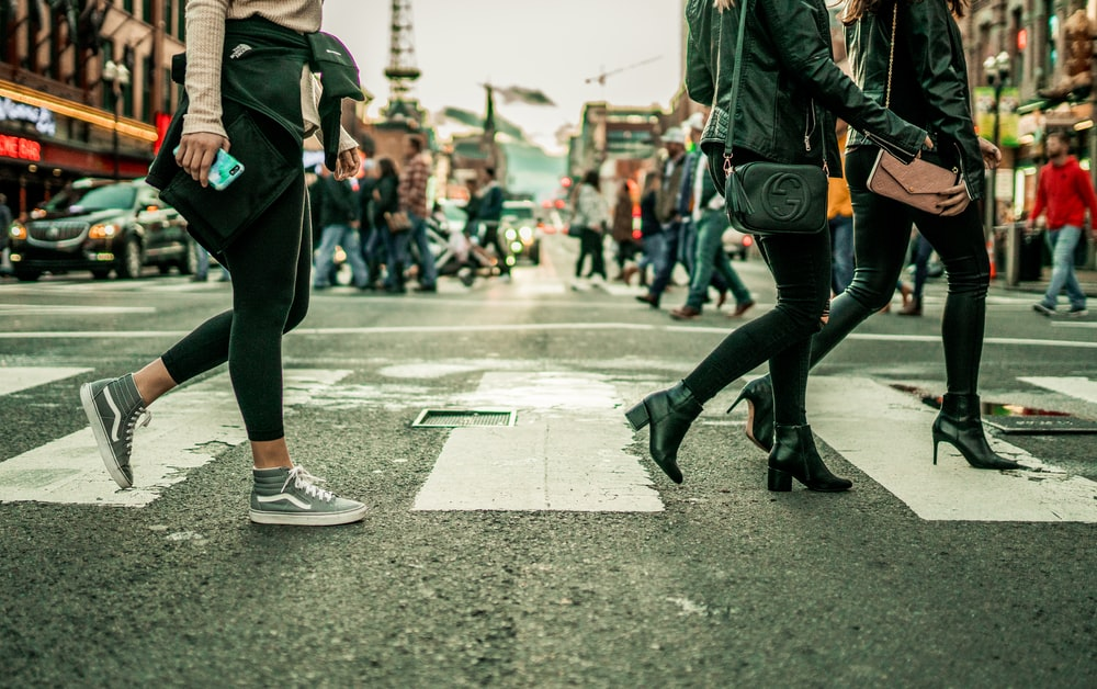 woman in black pants and black boots walking on street during daytime