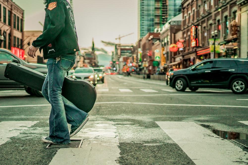 man in green jacket and blue denim jeans walking on sidewalk during daytime