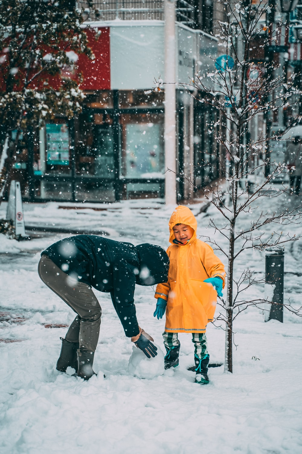 child in yellow jacket and black pants playing on snow covered ground during daytime