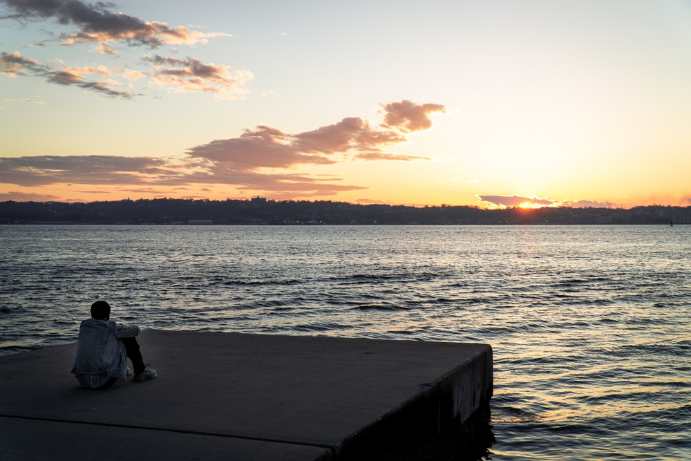 people sitting on wooden dock during sunset
