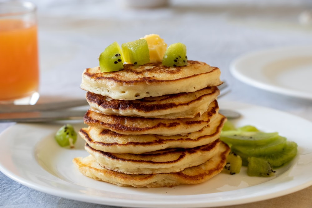 brown pancakes with sliced lemon on white ceramic plate