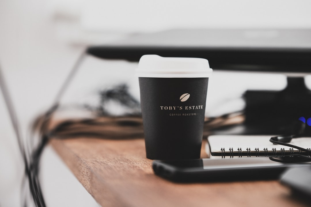 Black and White Plastic Cup On Brown Wooden Table - unsplash
