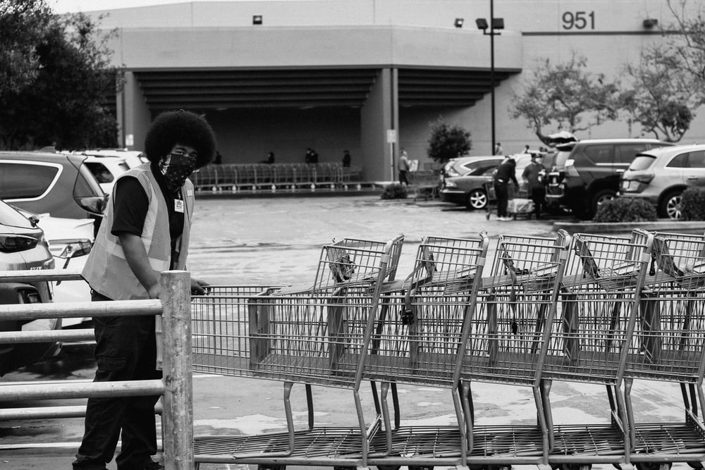 grayscale photo of people riding on shopping cart
