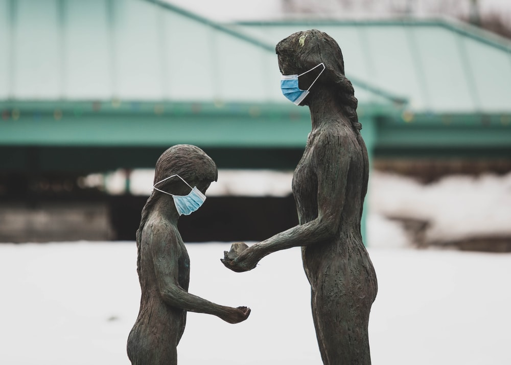 two brown wooden statue of man and woman