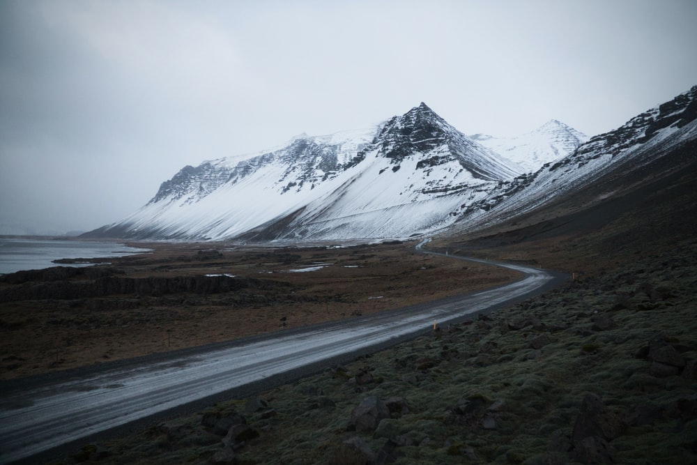 gray road near snow covered mountain