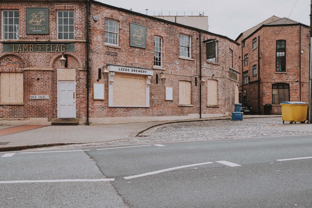 brown brick building beside road during daytime