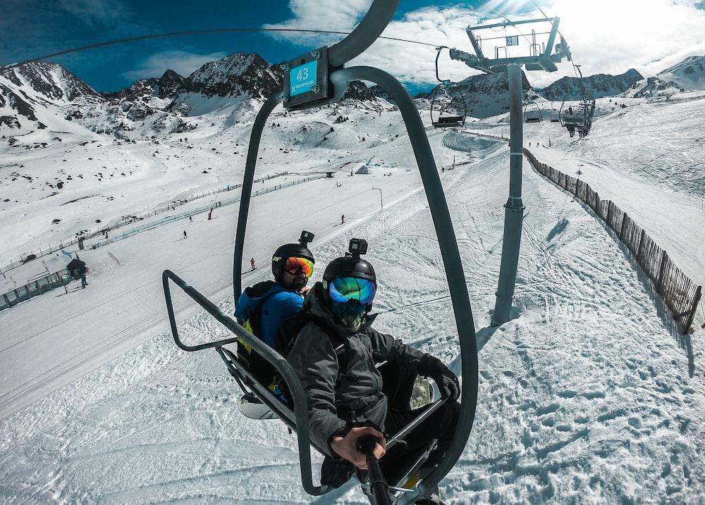 2 children riding on black ski lift during daytime