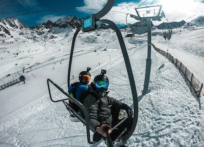 2 children riding on black ski lift during daytime andorra teams background