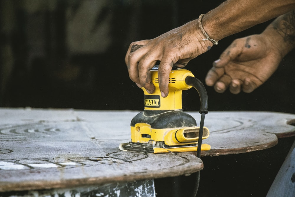 person holding yellow and black cordless power tool