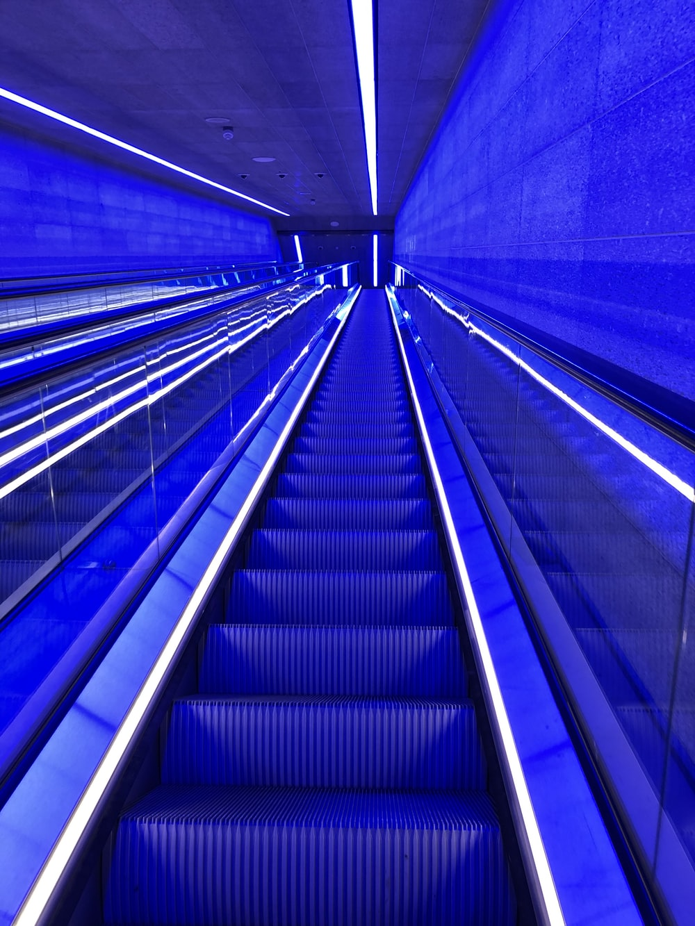 blue and white escalator in tunnel