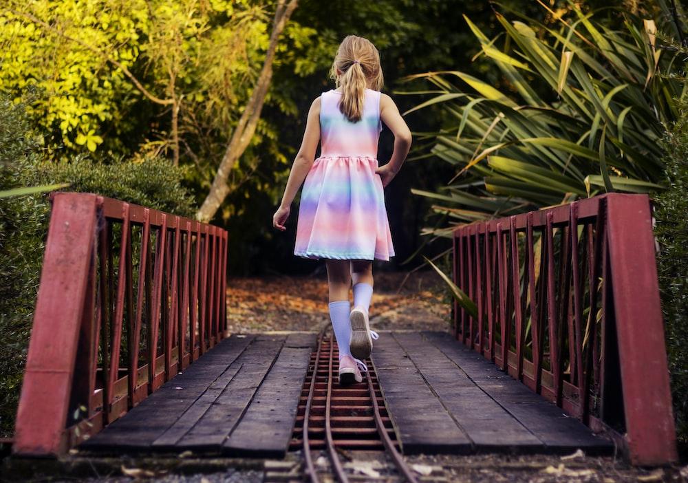 girl in pink dress walking on wooden bridge