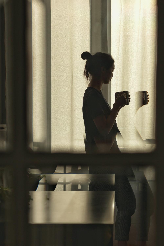 woman in black dress standing near window