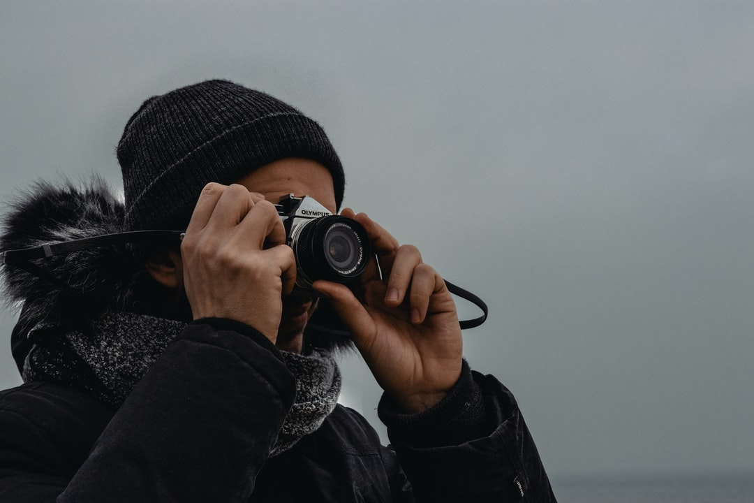 Person In Black Knit Cap Holding Black Dslr Camera - unsplash