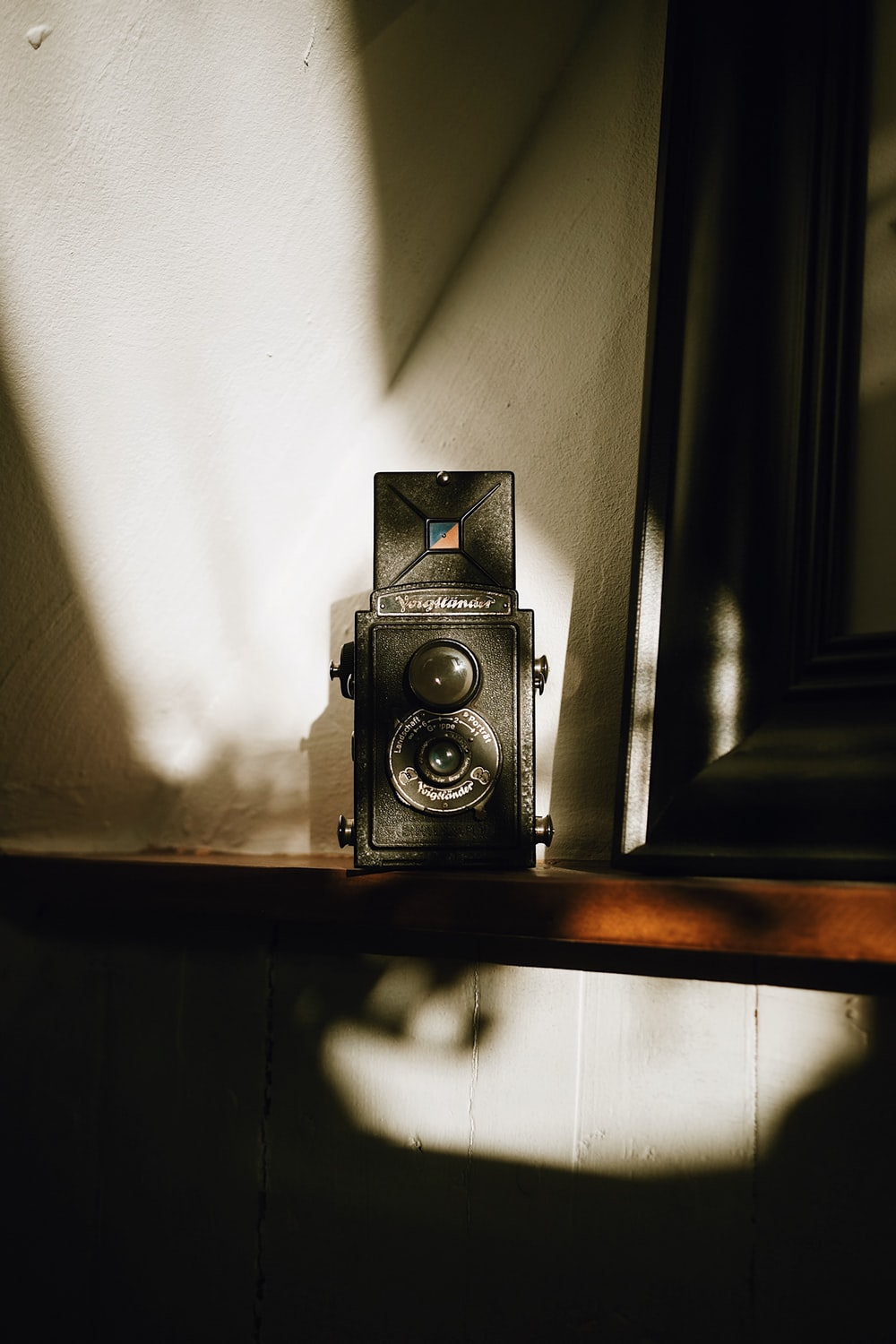 black and silver camera on brown wooden shelf