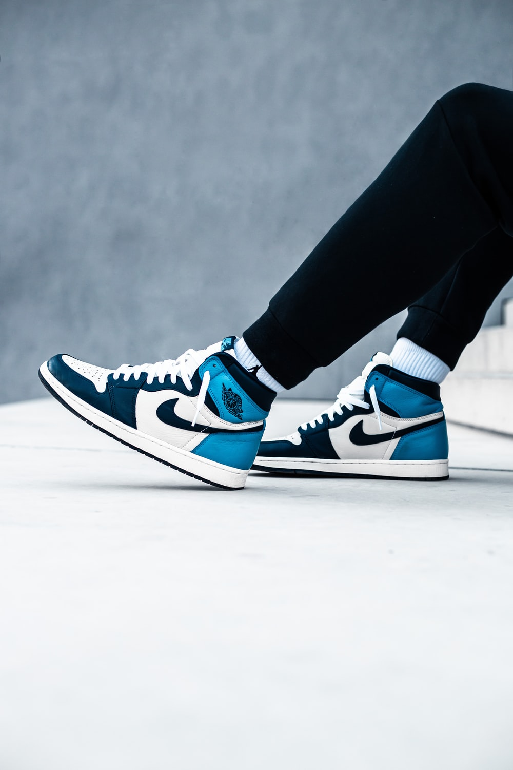 person wearing black pants and blue and white nike sneakers