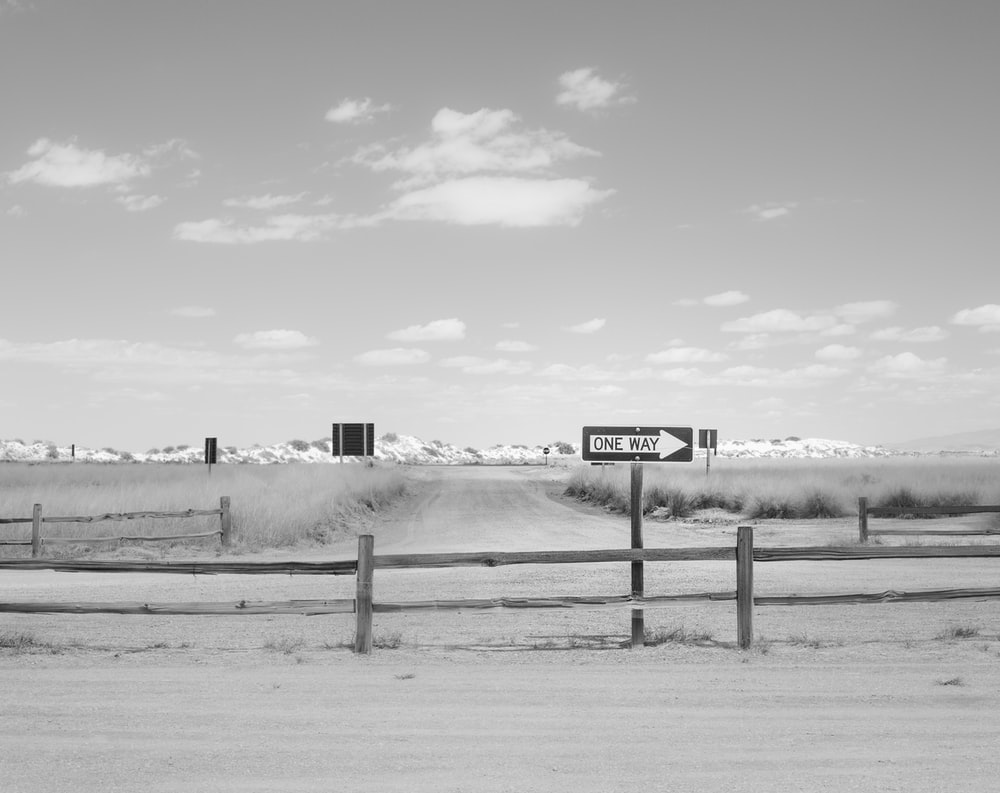 grayscale photo of a wooden fence with a distance at a snow covered field