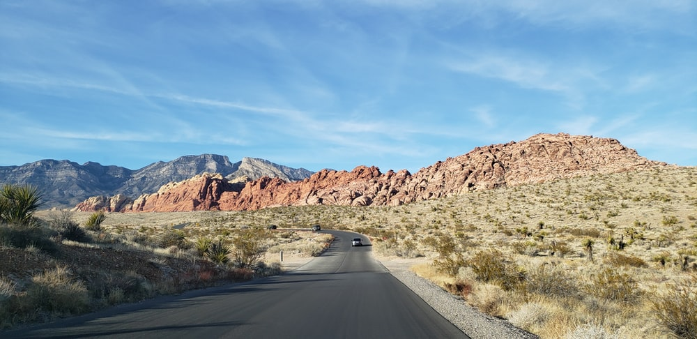 gray asphalt road between brown mountains during daytime