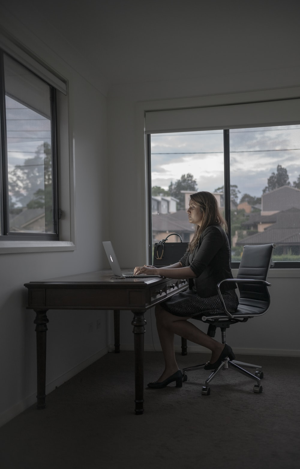woman in black shirt sitting on black office rolling chair using laptop computer