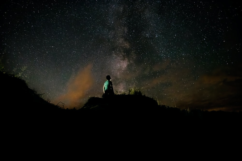 silhouette of man sitting on rock under starry night