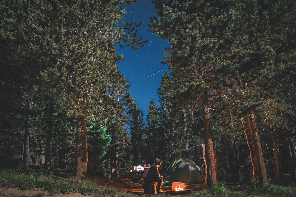 people sitting on camping chairs near bonfire under blue sky during night time