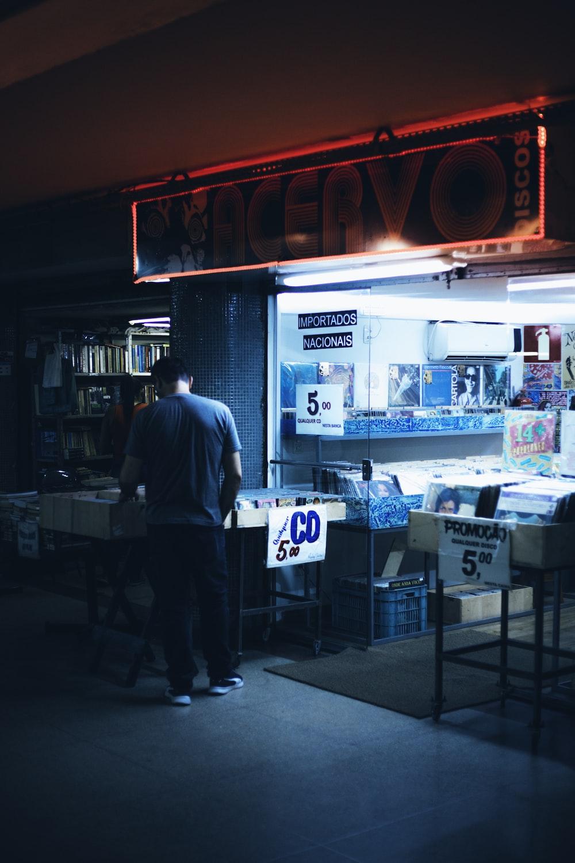 man in blue dress shirt standing near store
