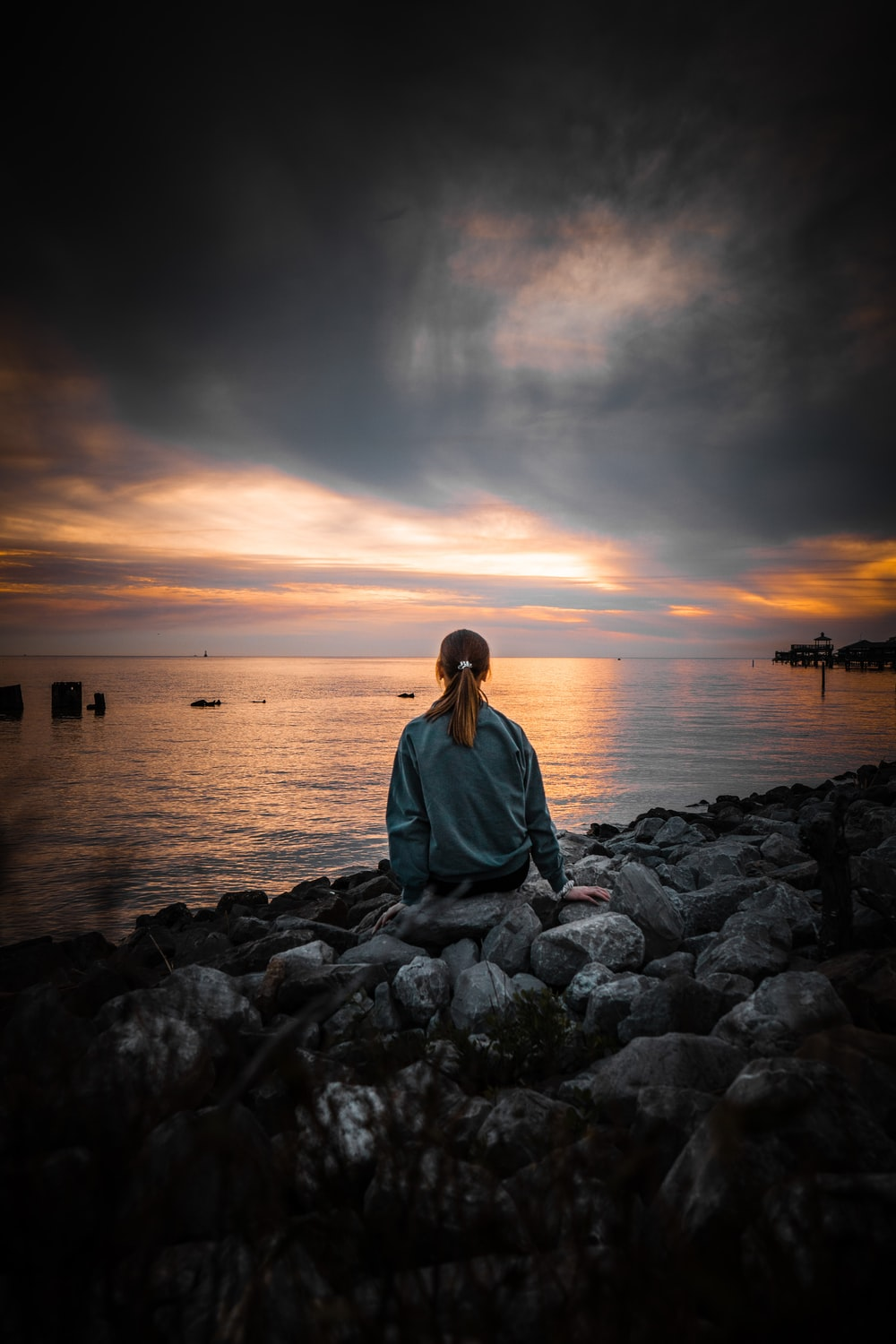 woman in blue long sleeve shirt sitting on gray rock near body of water during sunset