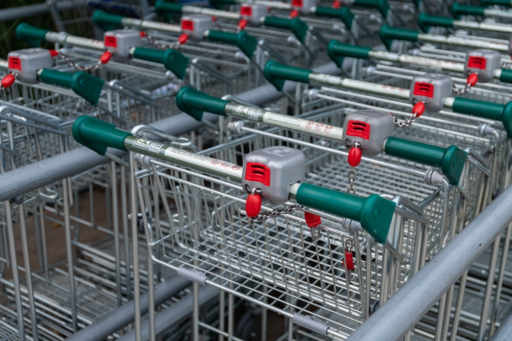 stainless steel shopping carts on gray metal rack