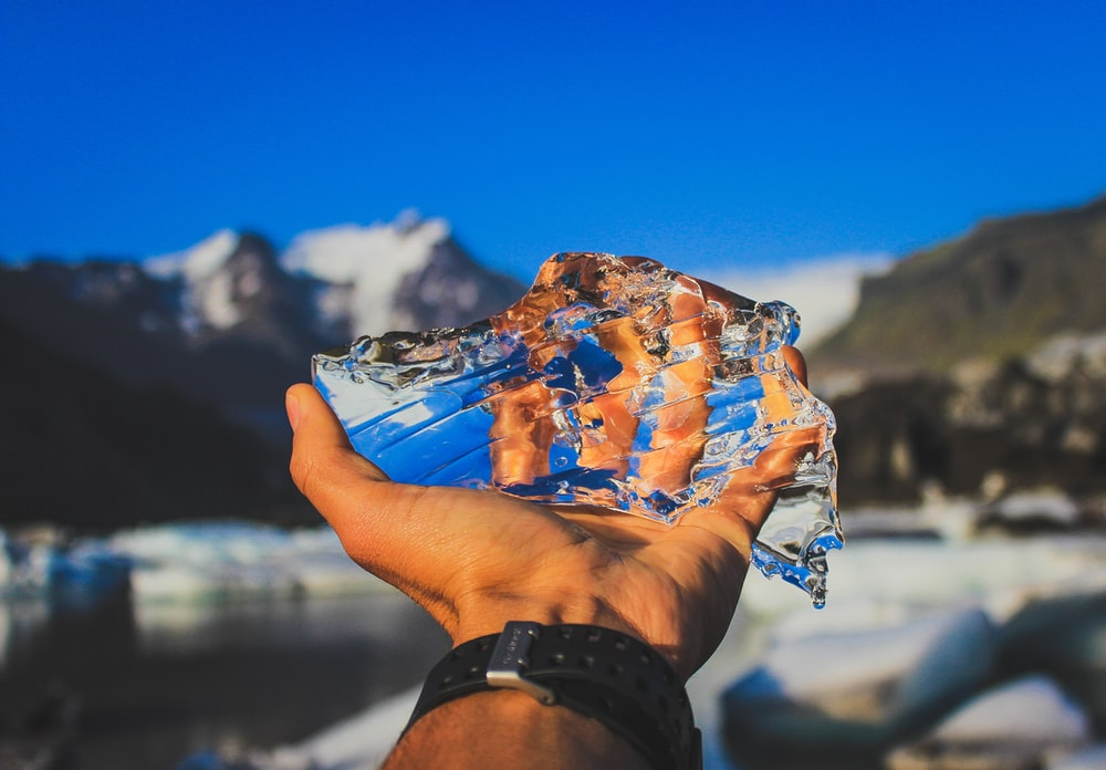person holding ice on clear glass