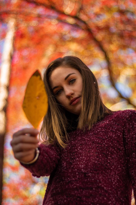 woman in maroon sweater holding brown wooden heart shaped board