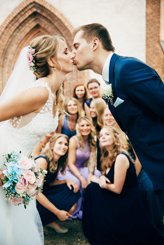 man in black suit jacket kissing woman in white wedding dress ...
