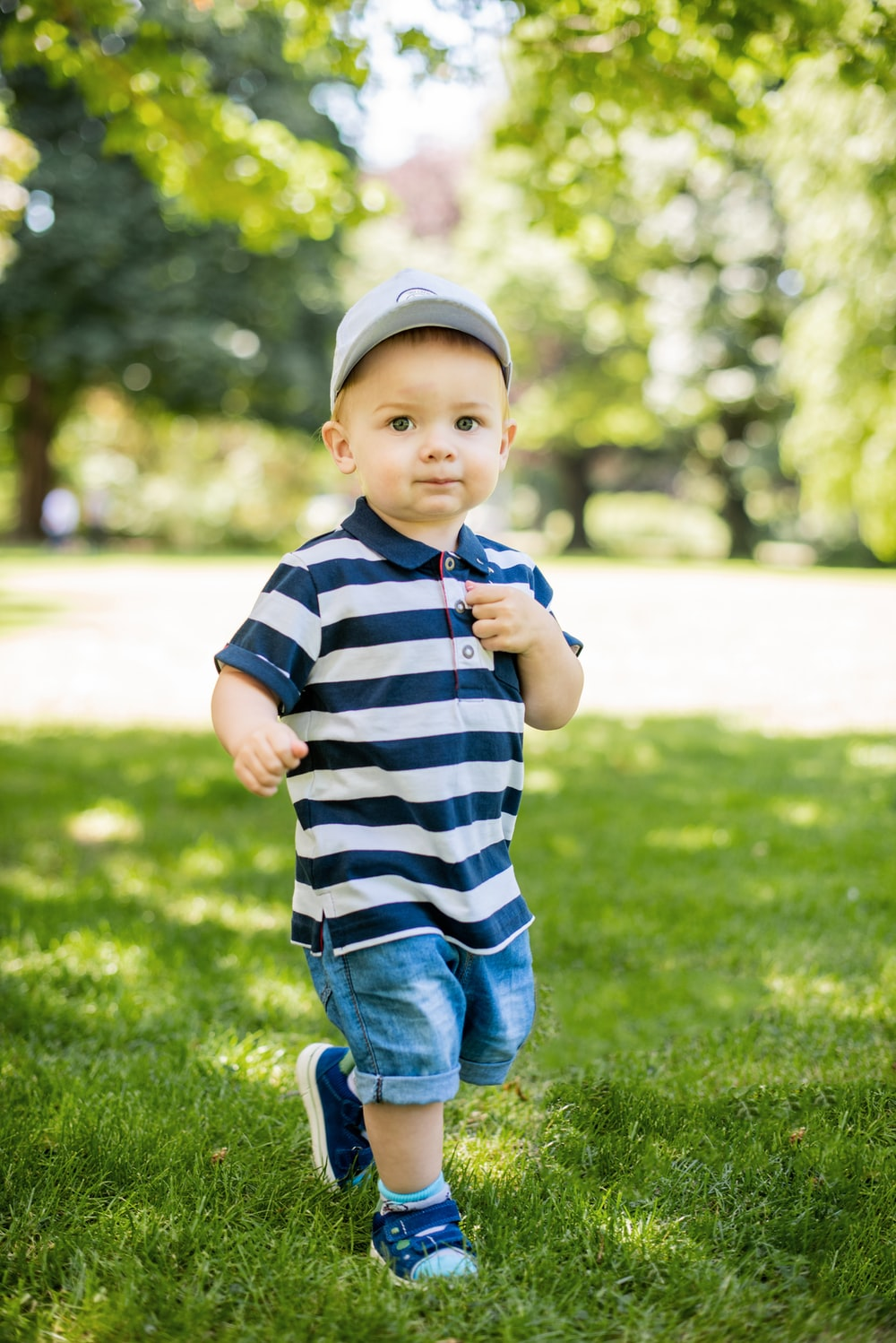 child in blue and white striped shirt and blue denim jeans standing on green grass field