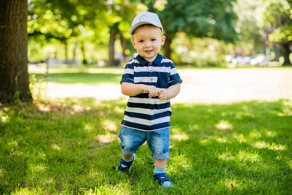boy in black and white stripe polo shirt and blue denim shorts standing on green grass