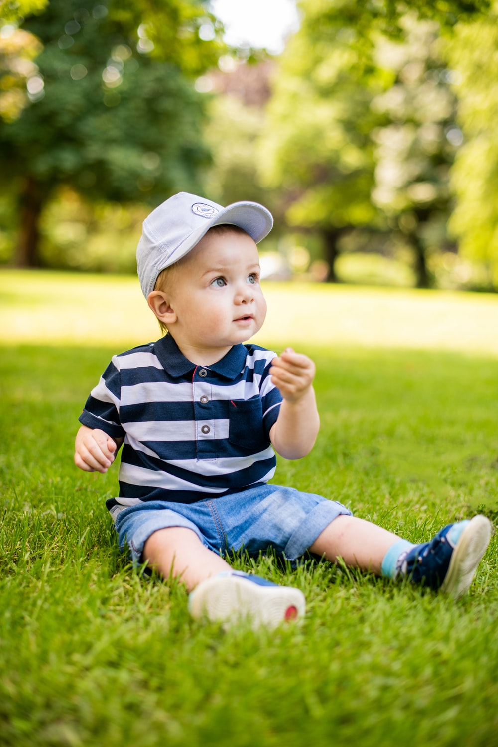 boy in blue and white stripe polo shirt and blue denim shorts sitting on green grass