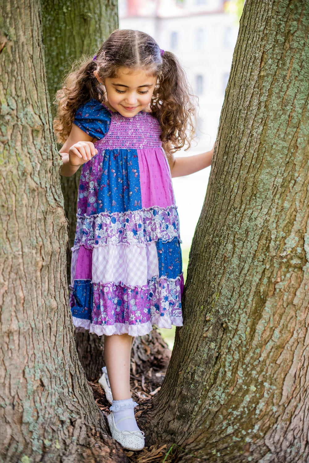 girl in purple and white floral dress standing beside tree