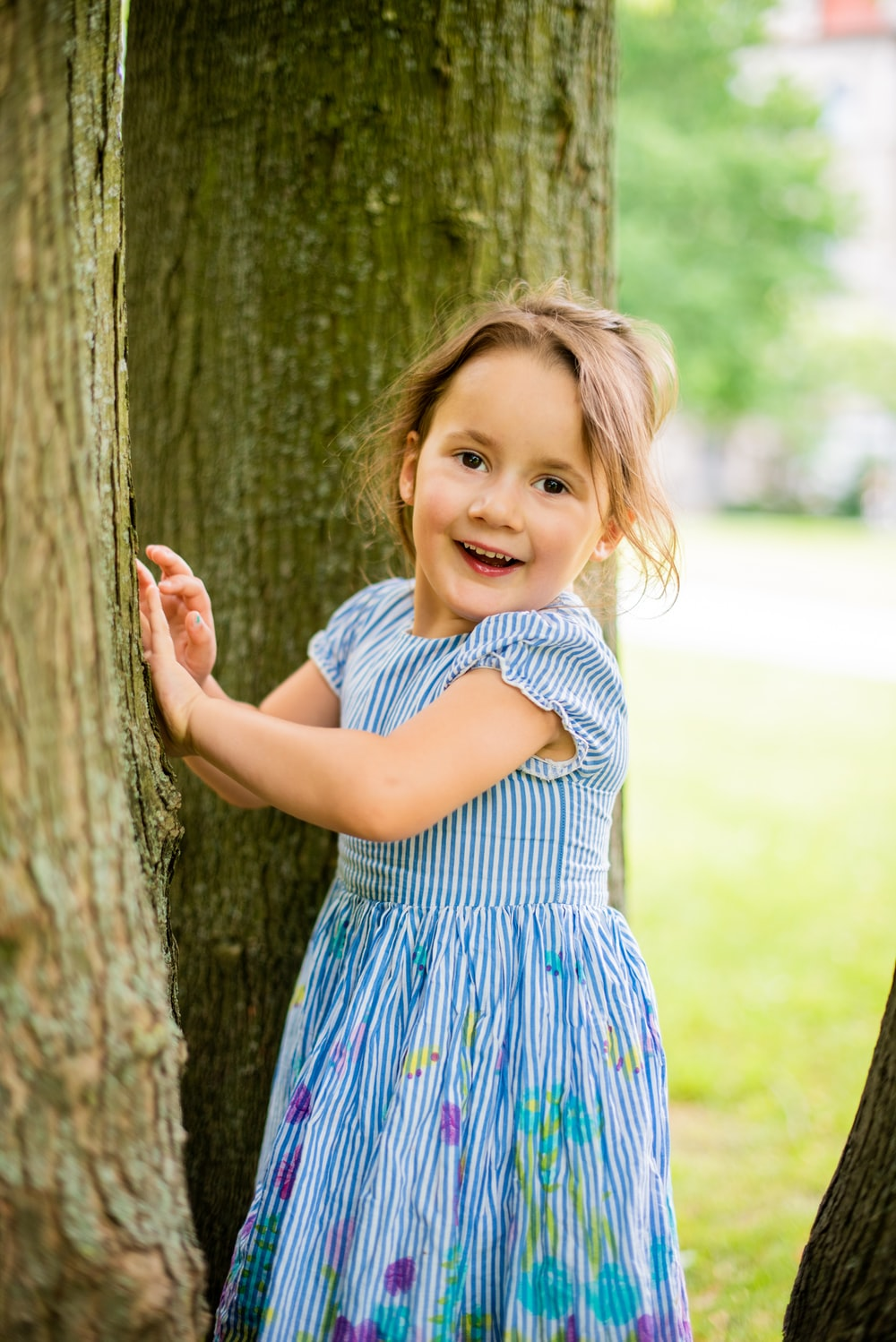 girl in blue and white polka dot dress standing beside brown tree during daytime
