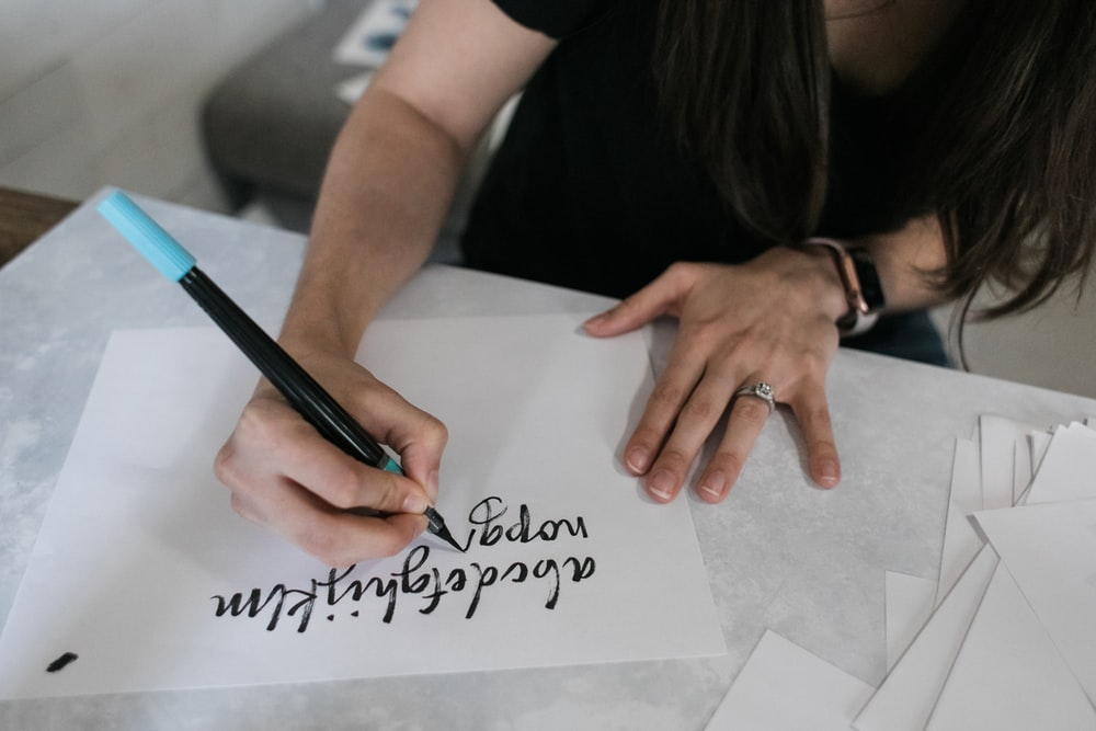 woman in black shirt writing on white paper