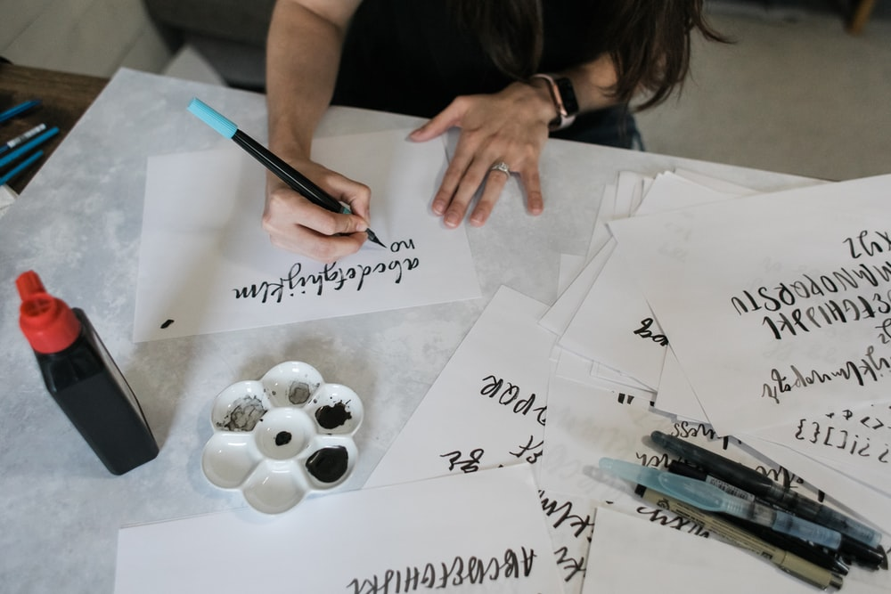 woman writing on white printer paper