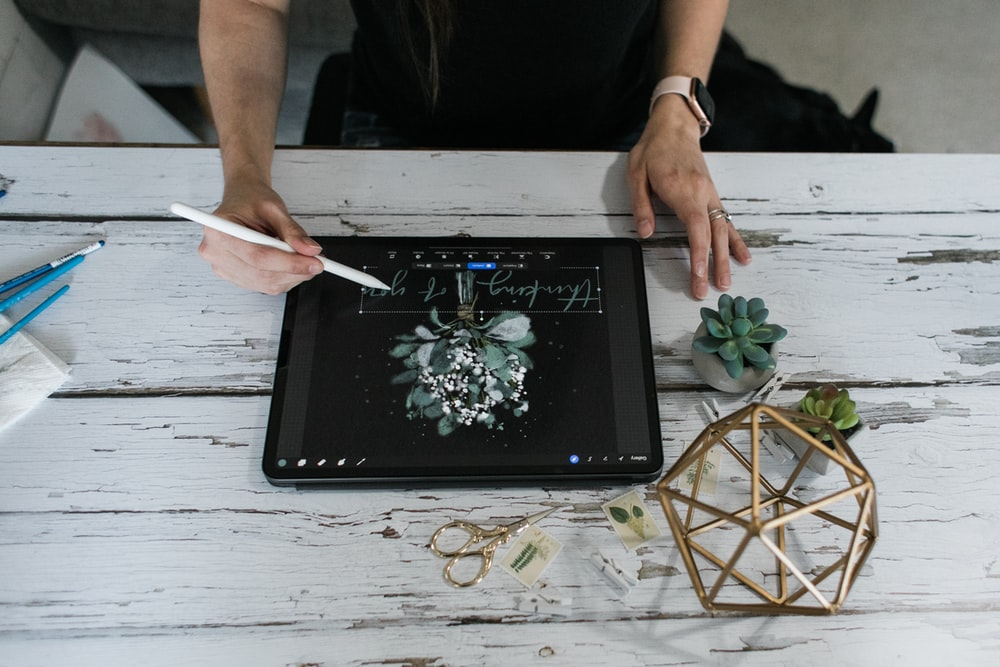 person holding white pen on black tablet computer