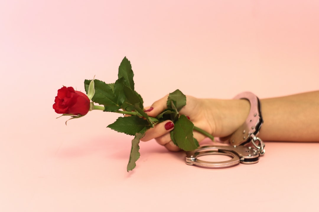 holding a rose in handcuffs