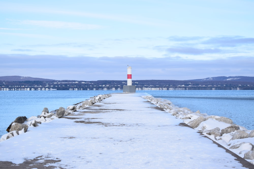 white and red lighthouse on gray concrete dock during daytime