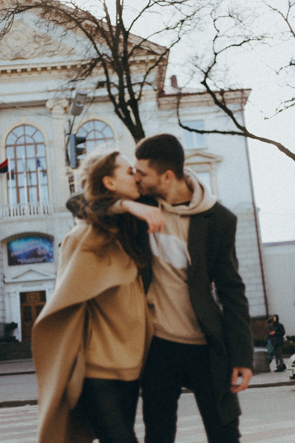 man in black suit kissing woman in brown coat