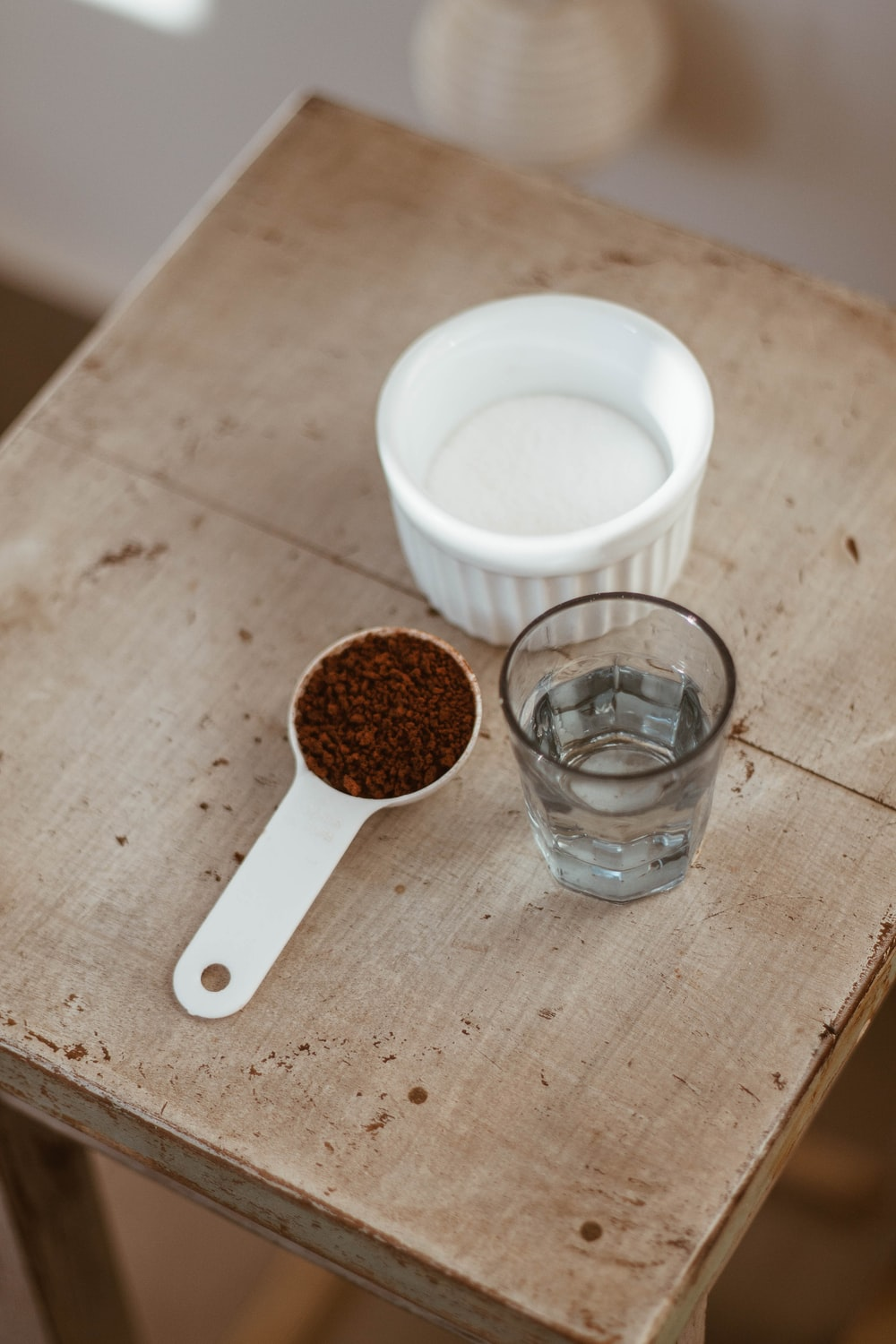 white ceramic mug beside clear drinking glass on brown wooden table