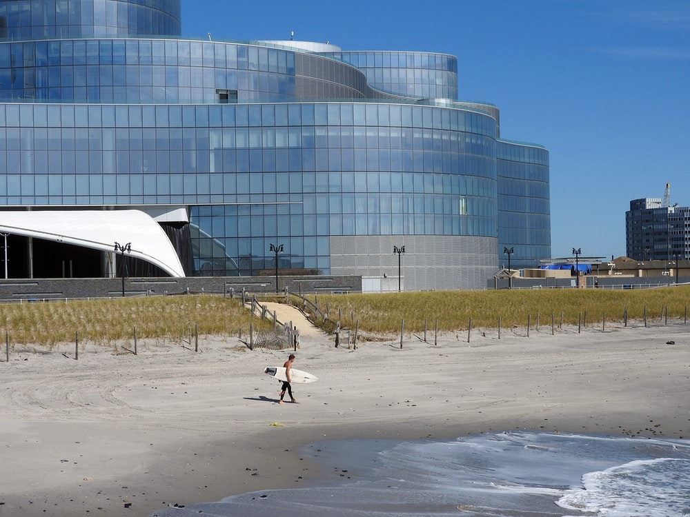 people walking on gray sand near white building during daytime