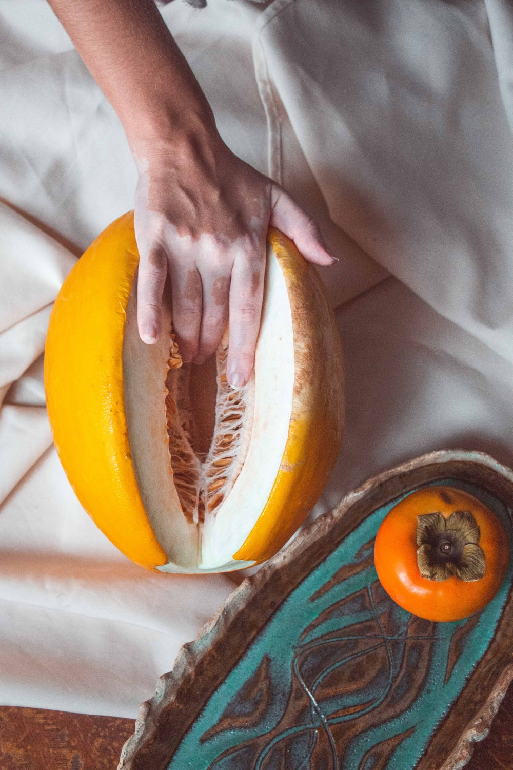 person holding sliced of yellow and brown fruit